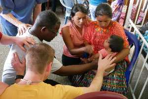 Team members praying for child at hospital