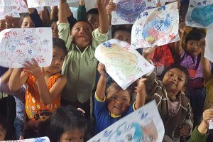 excited chihulha kids holding up their drawings