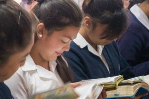High school students reading Bible