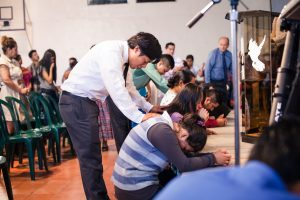 Pastor Hector praying with people