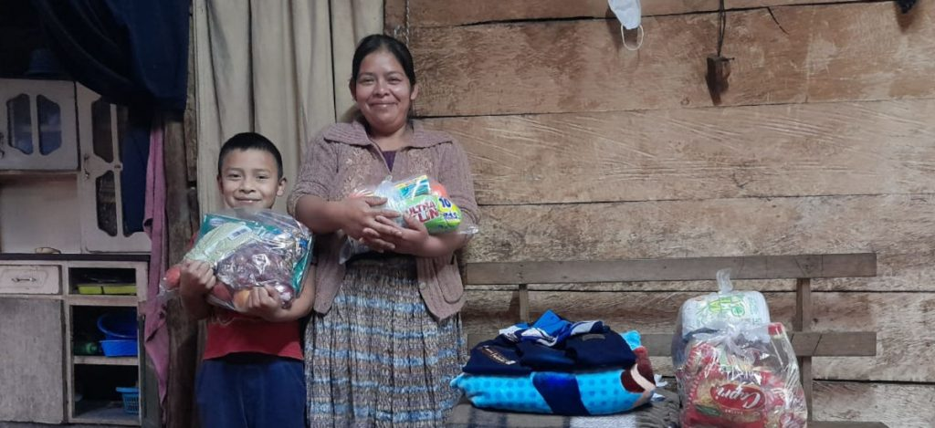 Jhon and his mother smiling with a food package