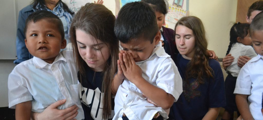 young adult praying with two vida students